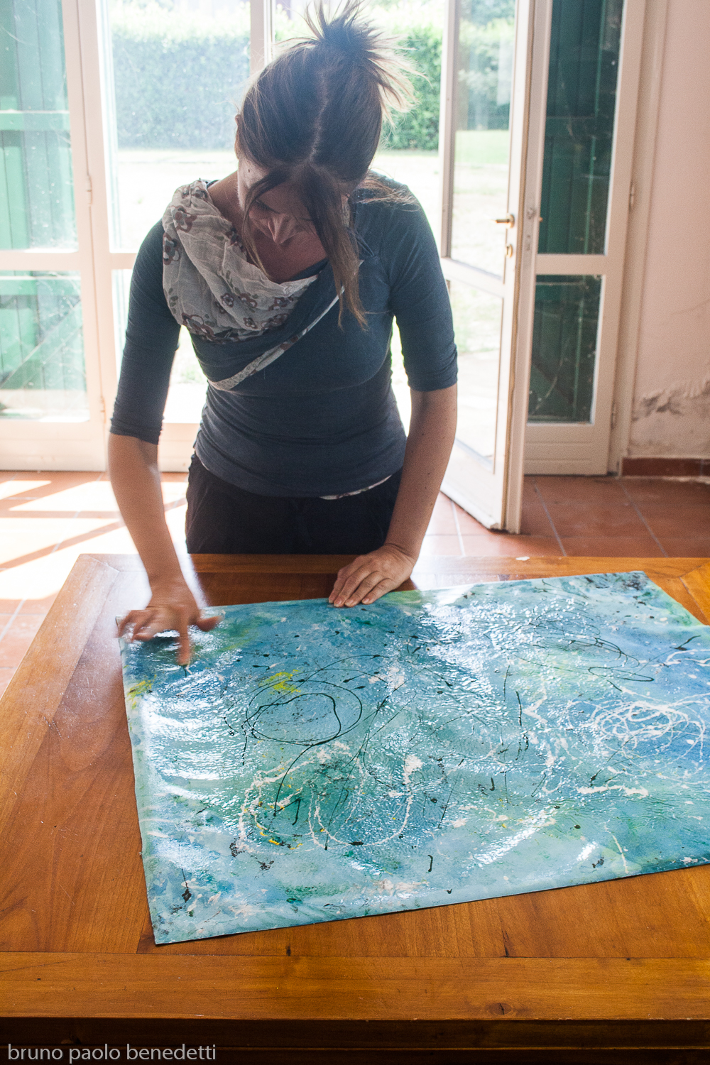 Barbara Stamegna putting some last touches on her Light Blue Abstract painting