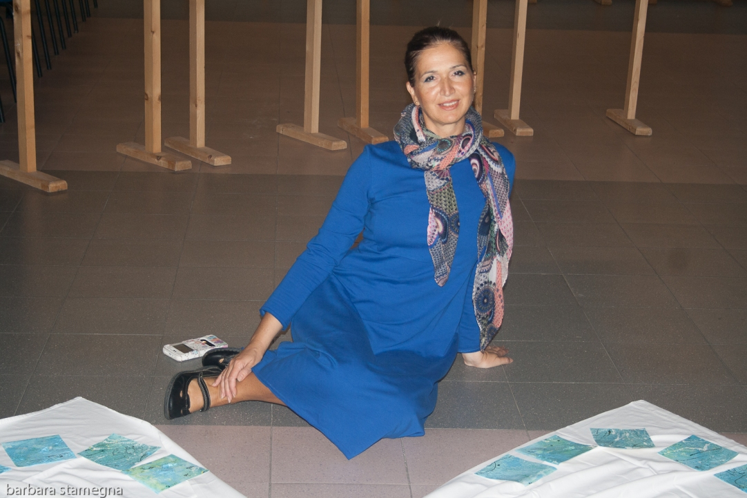 Barbara Stamegna sitting next to her Pieces Painting Project art installation during an exhibition