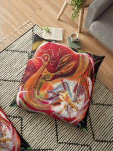 pillow with dominant red abstract art design on floor