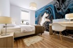 blue mural print on bedroom wall with blue dominant color with shades and fluid floating light shape