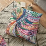 floor pillow with abstract concentric nature design in tones of pink, blue, green, orange, black and white with curls and shapes of nature